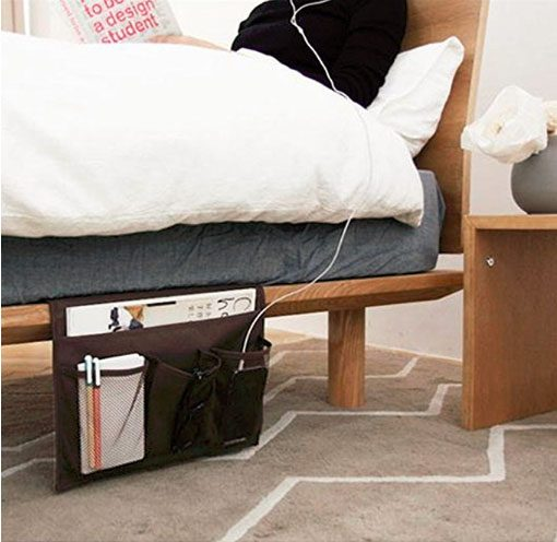 side view of bed with portable hanging caddy holding electronics and nightstand odds and ends