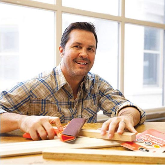 smiling man in plaid holding flexpro ergonomic sanding tool