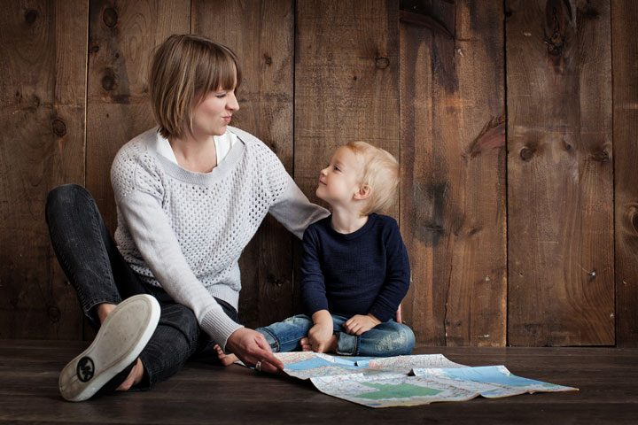 mom spending quality time with son looking at travel map