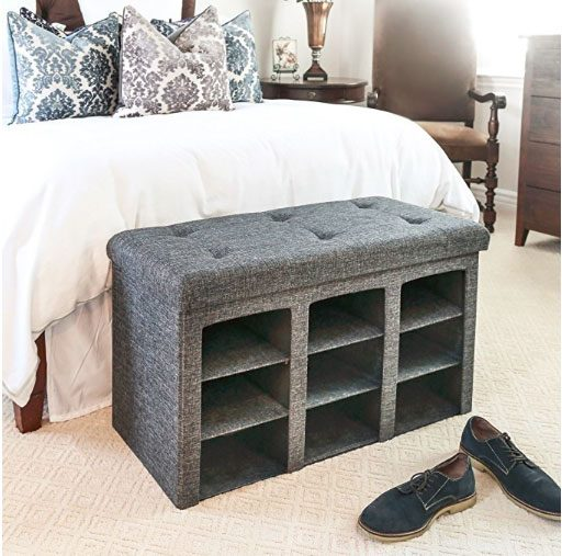 gray ottoman storage bench at foot of bed with side open to reveal compartments to store shoes