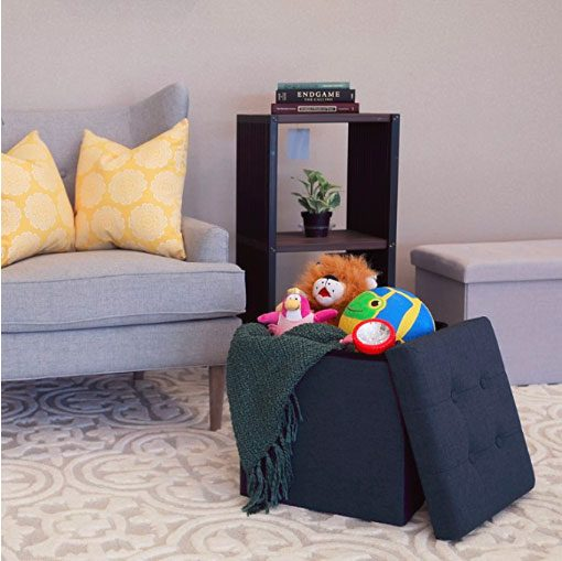 living room with navy blue ottoman stool open, with kids toys stuffed inside