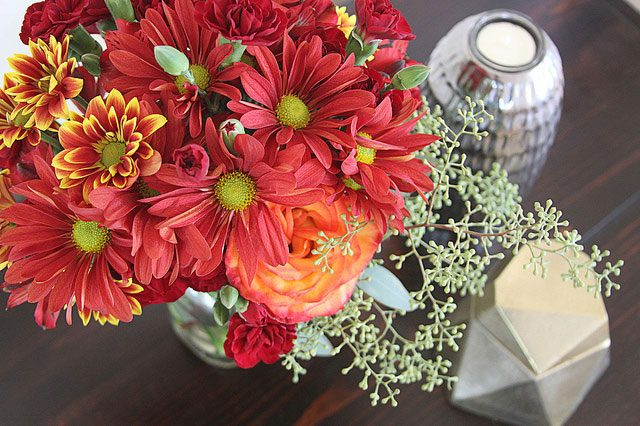 top view orange and red floral arrangement on tabletop