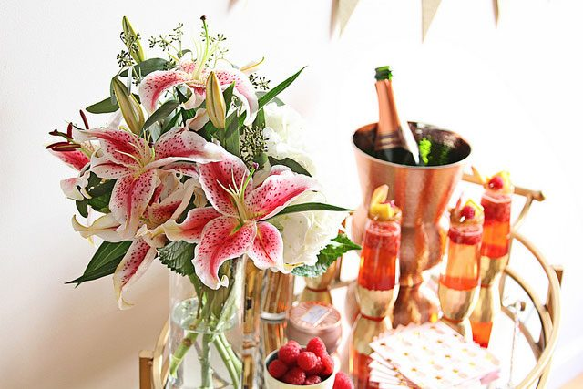 floral bouquet in foreground in focus with champagne and drinks on glass table and bowl of raspberries