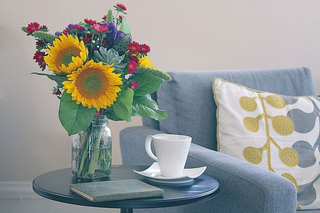 sunflower bouquet on end table with book and coffee cup next to gray blue sofa with yellow white pillow