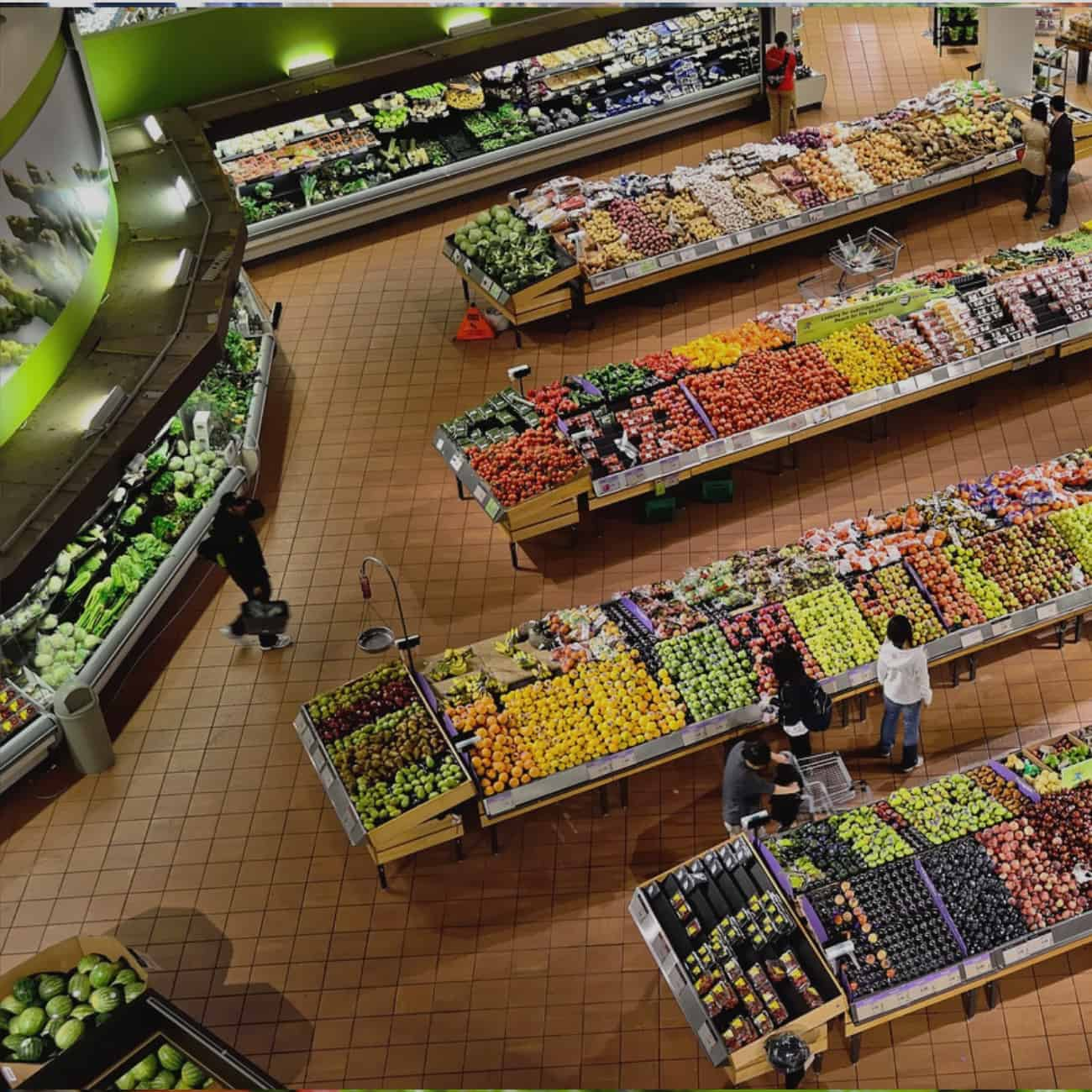 overhead view of supermarket produce section with shoppers.