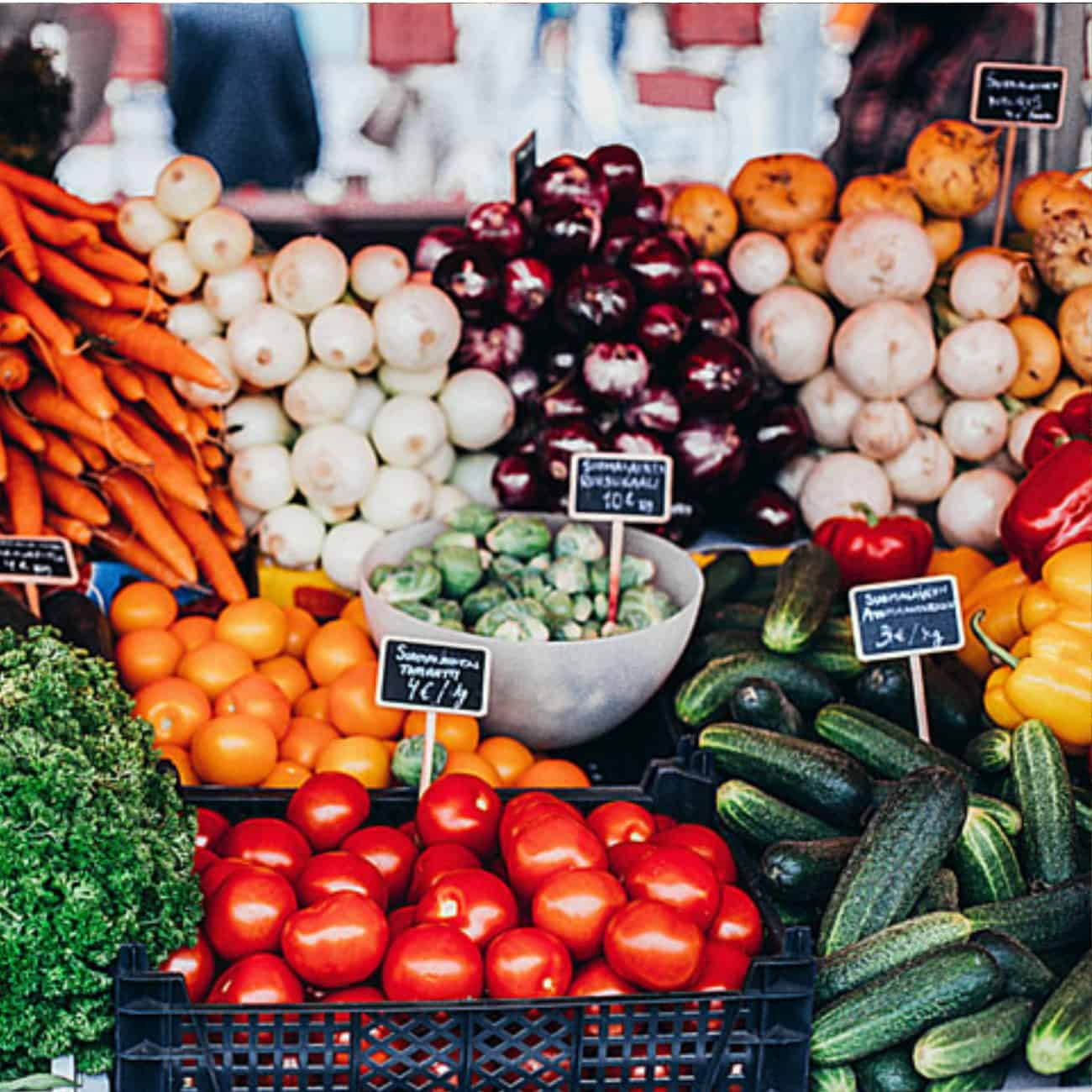 tomatoes, carrots, mushrooms, eggplant, brussels sprouts and more seasonal produce on display at outdoor market.